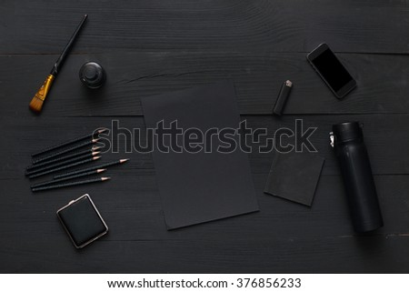 All object is black on wooden table. Black table top view of the artist. Empty wooden bench for creative work. Top view office workplace. Background for post in blog.