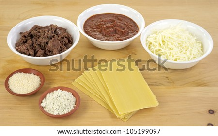 All of the ingredients for home made lasagna with browned beef, thick herb sauce, mozzarella cheese, Parmesan and Romano cheese and pasta on a wood cutting board.