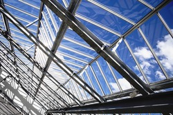 All-over glazing transparent roof of a contemporary building (greenhouse / pavilion / office / swimming pool) under bright sky