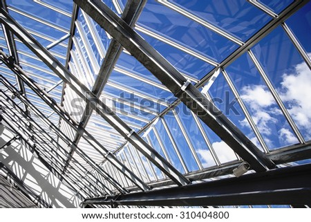 All-over glazing transparent roof of a contemporary building (greenhouse / pavilion / office / swimming pool) under bright sky #310404800