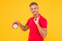 All right. Happy man hold alarm clock showing OK sign. Punctuality and accurate timekeeping. Chronometry and timekeeping. Clock gives the right time