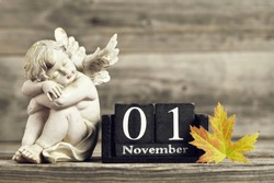 All Saints Day. Angel, wooden calendar and yellow autumn leaf