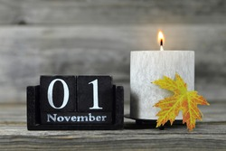 All Saints Day. Burning candle, wooden calendar and yellow autumn leaf
