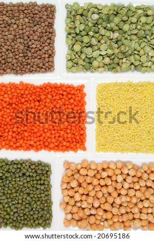 All sorts of beans and cereals sorted in white ceramic containers. Decorative and colorful food abstract.