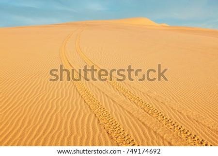 All-terrain vehicle (ATV) tracks in white sand dunes on sunrise, Mui Ne, Vietnam. Dunes around Bao Trang (White Lake, located 65 km NE of Phan Thiet) are  a major tourist attraction at Mui Ne