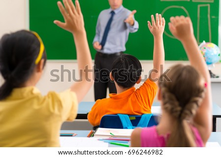All the pupils rising hands as they want to answer, rear view #696246982
