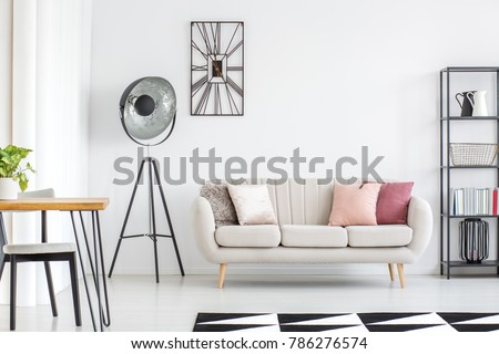 All white room with grey sofa, metal furniture and black and white carpet