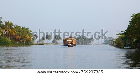 Alleppey (Alappuzha) / India - November 12, 2017 - A house boat transports tourists around the backwaters in Alleppey, India. House boat cruise is the top attraction of the inbound tourism in Kerala. #756297385