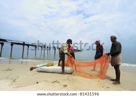 ALLEPPEY, INDIA - JULY 15: Fishermen clean fish net at seashore during Chakara July 15, 2011 in Alleppey, India. Chakara is a phenomenon of large number of fishes appearing in sea surface during mansoon.