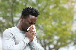 Allergic black man blowing on wipe in a park on spring season a sunny day