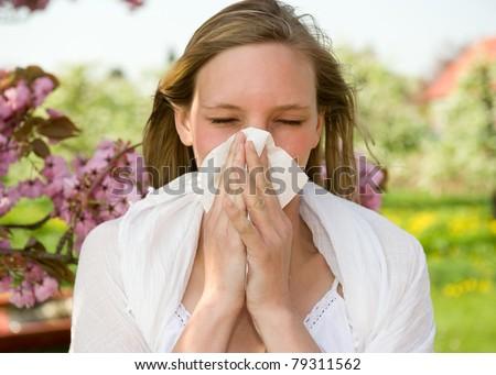 Allergic girl sneezing in handkerchief