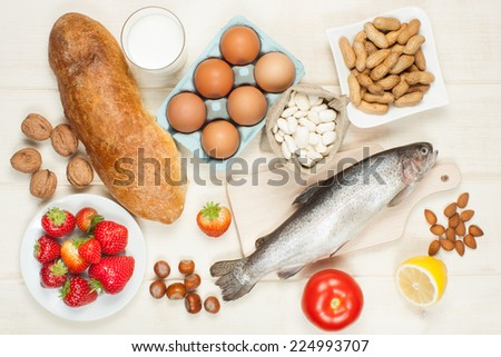 Allergy food concept - bread, milk, fruits, nuts, eggs and beans on wooden table