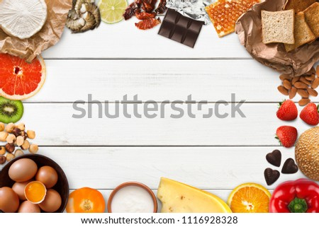 Allergy food concept. Set of allergic products as nuts, cheese, honey, citrus fruits, eggs, chocolate, kiwi, strawberry and seafood on wooden boards, isolated on white wood, top view, copy space #1116928328