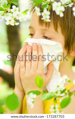 Allergy.Little boy is blowing his nose outdoors