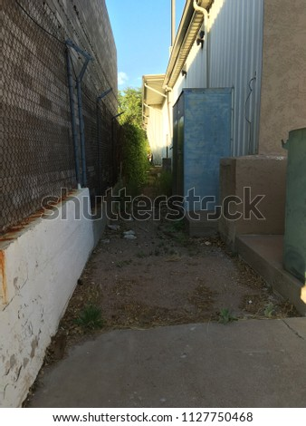 Alley between two buildings with rocks and debris