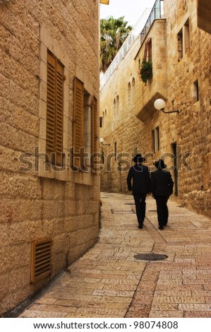 Alley in Jerusalem old city with two orthodox men walking away , Israel