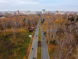 Alley in the park of the 30th anniversary of the Komsomol from a height. People walk on a day off in the park in the fall. Central alley in the park of Omsk