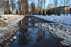 Alley in the park with melting snow, puddles and ice on a sunny spring day. Snow and dirt in the park. Thawed patches. Spring is coming, the month of March.