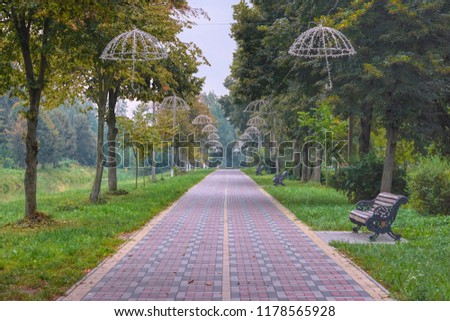 Alley of lanterns in the form of umbrellas in the park of the city of Lutsk (Ukraine). Multicolored pavement and decorative benches.