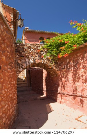 Alley with arches. The houses have orange red plaster and covered with vines. (Roussillon, Provence, France)