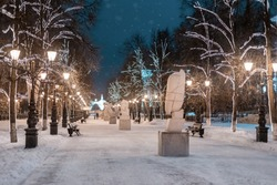 alley with lanterns and sculptures in winter near Ufa Medical University at evening