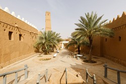 Alley with palm trees and renovated houses in the traditional village of Shaqra in Saudi Arabia. Shaqra is a traditional restored village made of clay bricks