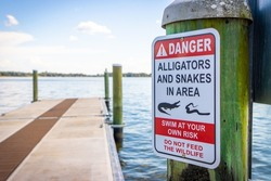 Alligator and snake danger warning sign on Florida lake by pier boating dock no feeding swim at your own risk