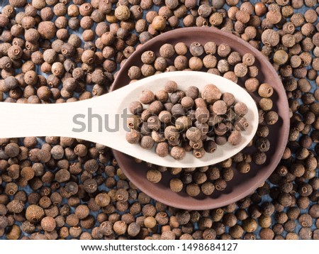 Allspice (Jamaica pepper) in a wooden spoon and clay plate on allspice background horizontally #1498684127