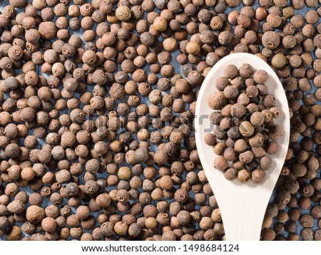 Allspice (Jamaica pepper) in a wooden spoon on allspice background #1498684124