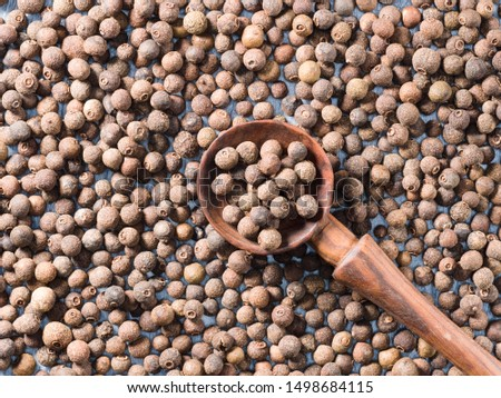 Allspice (Jamaica pepper) in a wooden spoon on allspice background diagonally #1498684115