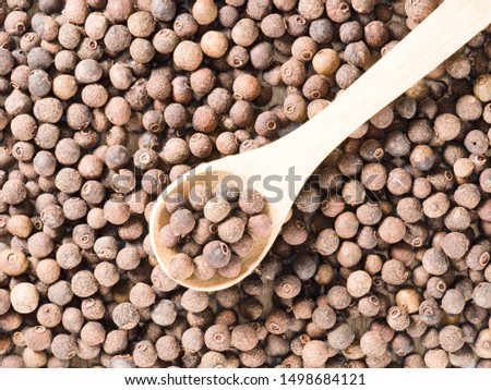 Allspice (Jamaica pepper) in a wooden spoon on allspice background diagonally #1498684121