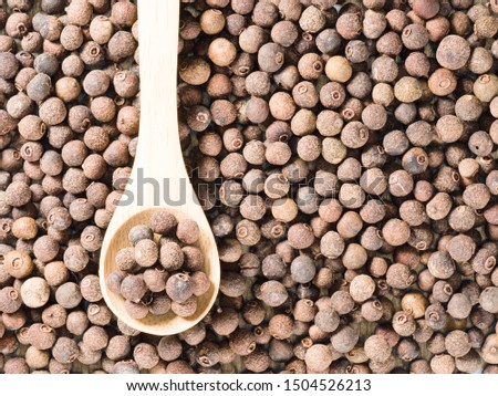 Allspice (Jamaica pepper) in a wooden spoon on allspice background vertically #1504526213