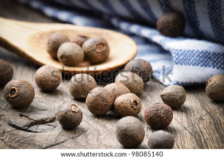 Allspice pepper on the rustic wooden table