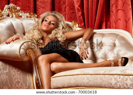 alluring blond relaxing on a sofa in luxury interior