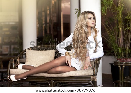 alluring blond relaxing on sofa in luxury interior. Stylish rich slim girl in sexy dress with healthy glossy hair at hotel villa apartment. Fashion glamorous shot at vacation resort spring-summer