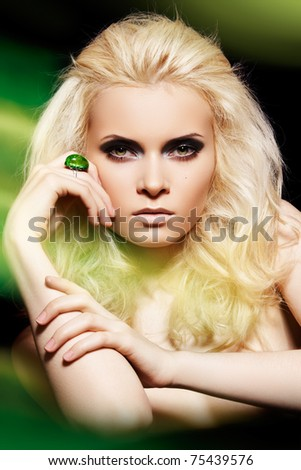 stock photo : Alluring blond woman model with big ring in magic green mist. Glamour and fashion style. Real lights effect: mixed light with long exposure.
