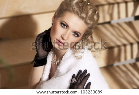 alluring blond woman relaxing on ladder in luxury hotel. Stylish rich slim girl in gloves  elegant dress and fur with healthy glossy hair at villa apartment. Fashion glamorous  model spring-summer