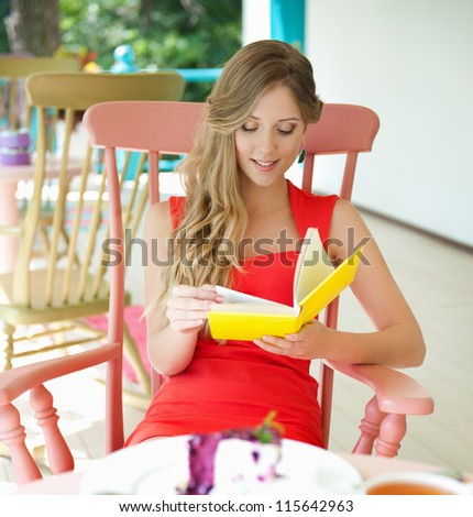 alluring blonde relaxing in cafe and reading the book