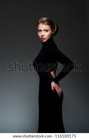 alluring woman in black evening dress posing over dark background