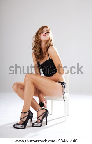 Alluring young woman in black lingerie sits in a white chair while looking into the camera. Vertical shot.