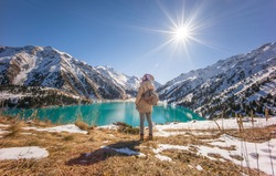 ALMATY, KAZAKHSTAN: A young lady standing in front of spectacular scenic Big Almaty Lake ,Tien Shan Mountains in Almaty, Kazakhstan during late autumn, winter.