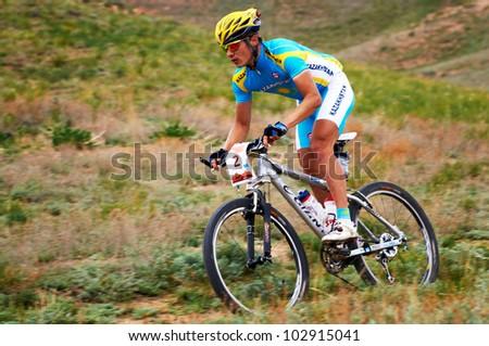 """ALMATY, KAZAKHSTAN - APRIL 29: K.Kazantcev (N2) in action at Adventure mountain bike cross-country marathon in mountains """"Jeyran Trophy 2012"""" April 29, 2012 in Almaty, Kazakhstan."""