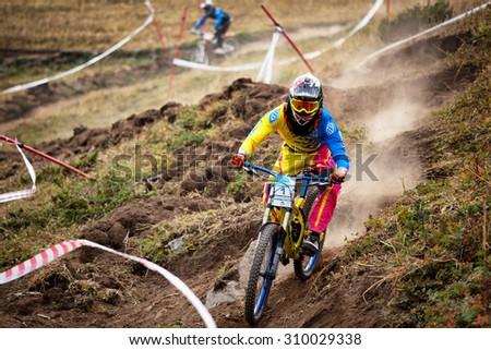 ALMATY, KAZAKHSTAN - AUGUST 22, 2015: J.Kumakbayev (N1) in action at Mountain Bike sports event DOWNHILL EXTREME WEEKEND.