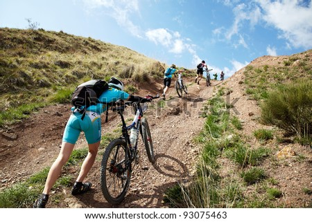 "ALMATY, KAZAKHSTAN - MAY 1: Athletes take their bikes and hike up a hill during the Adventure mountain bike cross-country marathon in mountains ""Jeyran Trophy 2011"" on May 1, 2011 in Almaty, Kazakhstan."