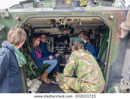 ALMERE, NETHERLANDS - 12 APRIL 2014: People sitting in the rear of a military vehicle on display during the first National Security Day held in the city of Almere