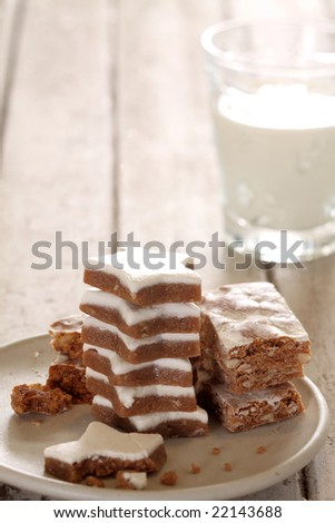 almond and ginger cookie stack with a glass of milk on white wood background.