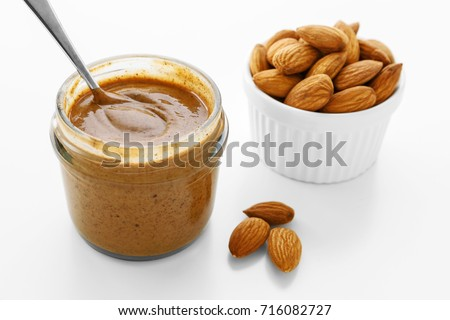 Almond butter with almonds on white background #716082727