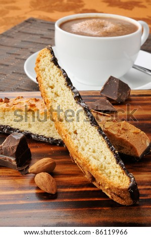 Almond chocolate biscotti with a cup of hot chocolate in the background - stock photo