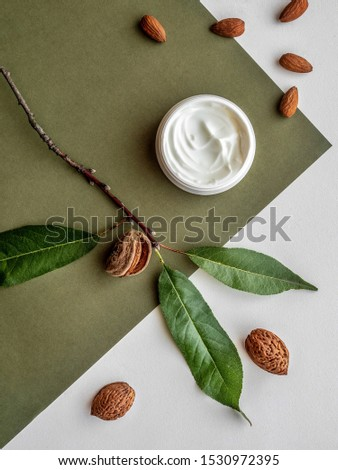 Almond face cream and almond nuts and leaves on green background. Overhead shot. #1530972395