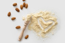 almond flour with nuts scattered on white background, love heart symbol, gluten-free product, keto food, top view, empty space for text
